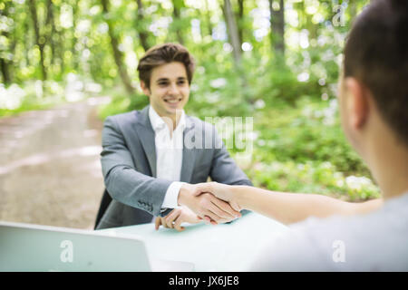 Manager in suit welcomes with handshake at interview new man at his office table in green park forest. Business - Stock Photo