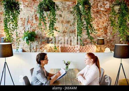 Conducting Interview at Fashionable Restaurant - Stock Photo