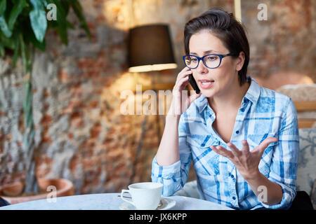 Pretty Entrepreneur Conducting Telephone Negotiations - Stock Photo