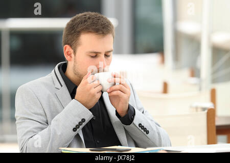 Executive drinking enjoying coffee break sitting in a bar - Stock Photo