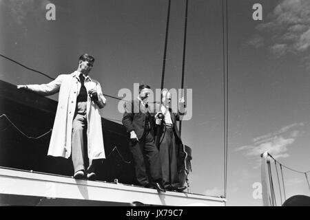 Three men standing near lifeboat on ship. - Stock Photo