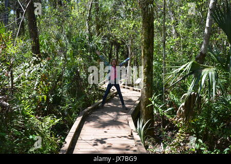 Young female acting silly on a boardwalk through the woods. - Stock Photo