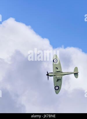 The Battle of Britain Memorial Flight's Spitfire P7350 (F Mk IIa) banking hard right towards cloud cover - Stock Photo