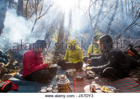 Expedition members sit around a campsite eating food. - Stock Photo