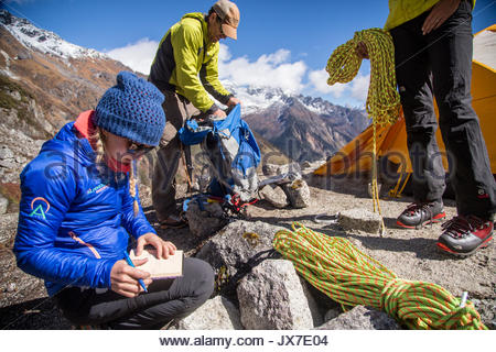 Expedition members check gear and review plans prior to setting out mountaineering. - Stock Photo