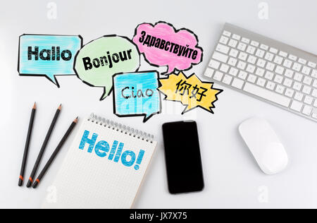 Hello word cloud in different languages of the world, background concept. Office desk table with computer, Smartphone - Stock Photo
