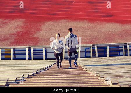 couple walking downstairs on stadium - Stock Photo