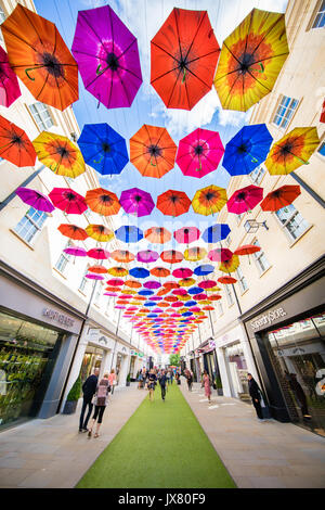 Shoppers passing underneath  the colourful umbrella art installation at Bath Spa's Southgate shopping centre UK - Stock Photo