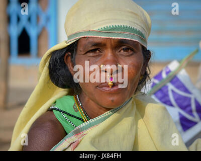 Closeup street portrait (outdoor headshot, full-face view) of a mature Indian Adivasi market woman with two nose - Stock Photo