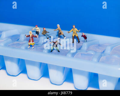 HO scale figures skating on ice cube fun, food, art, playful toy miniatures - Stock Photo