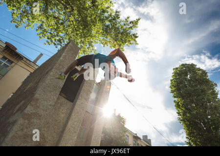 City parkour. The guy does the opposite somersault. Shooting from the lower angle. Dexterity and extreme. - Stock Photo