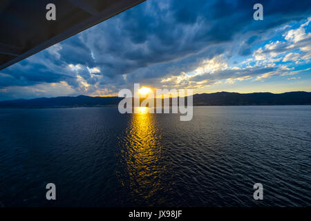 The sun going down from the balcony of a cruise ship on the Mediterranean Sea as a storm blows in - Stock Photo