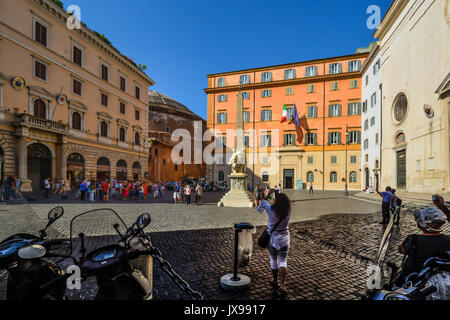 Sunny day in Piazza della Minerva as the back of the Pantheon looms in the background. Tourists and a young lady - Stock Photo