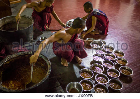 Two young monks place small bowls of food onto a tray for a third monk to deliver. - Stock Photo