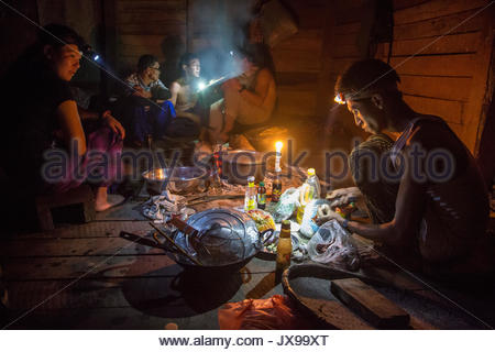 Porters prepare a meal by lamplight in a darkened cabin. - Stock Photo