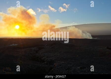 Red hot lava, steam, smoke and fire from the Kilauea volcano at the rim of the caldera during sunset at  Volcanoes - Stock Photo