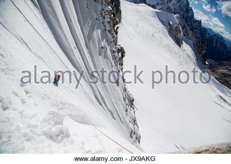 A mountaineer climbs the west ridge of Hkakabo Razi, said to be Southeast Asia's tallest mountain. - Stock Photo