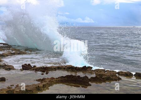 As Strong Waves Hits the Cliffs of Guiuan, Samar, Eastern Philippines, a splash of seawater emerges from the edge - Stock Photo