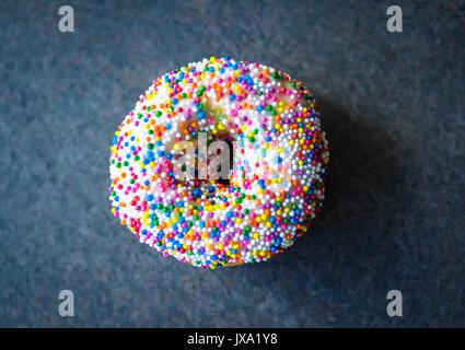 A vanilla dip donut (sprinkle donut, rainbow sprinkle donut) from Tim Hortons, a popular Canadian fast food restaurant - Stock Photo
