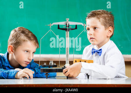Two small schoolmates use scales on lesson in school - Stock Photo