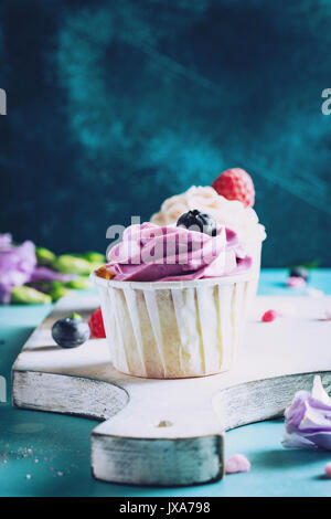 Colorful cupcakes with buttercream on cutting board. Closeup view, toned image - Stock Photo