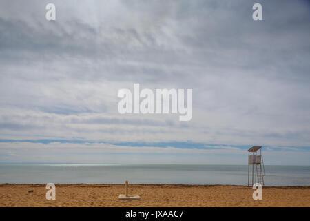 empty lifeguard post on the beach near the Black sea in off-season, gloomy dramatic grey sky - Stock Photo