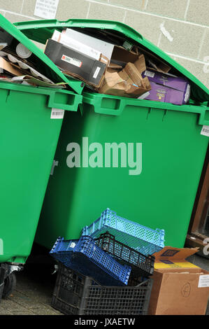 some rubbish recycling card and glass bottles in bins ready for collections overflowing dustbins full of garbage - Stock Photo