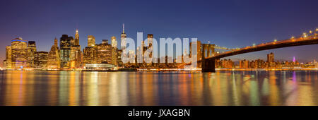 The New York City skyline and the Brooklyn Bridge photographed at night. - Stock Photo
