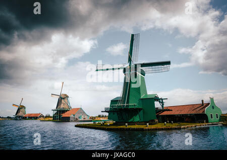 Panoramic view of Authentic Zaandam mills in Zaanstad village on the river Zaan against the stormy sky with clouds. - Stock Photo