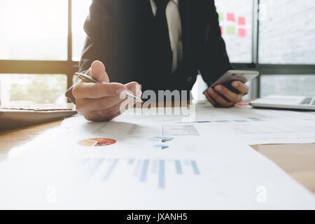 Business man investment consultant analyzing company annual financial report balance sheet statement working with - Stock Photo