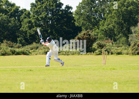 A cricket ball smashes through the wickets sending the bails flying after a missed shot by the batsman during a - Stock Photo