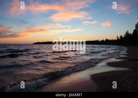 North seascape on Lake Onega - waves beat against the granite shore which reflects the rays of the setting sun. - Stock Photo