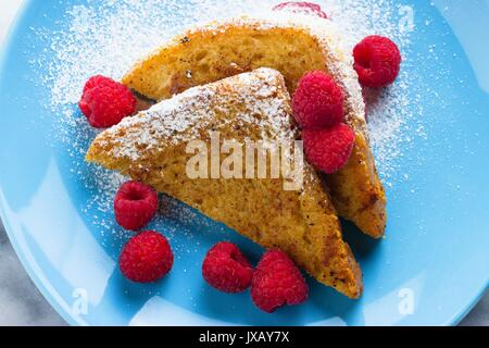 Fresh french toast richly covered by powdered sugar and raspberries - Stock Photo