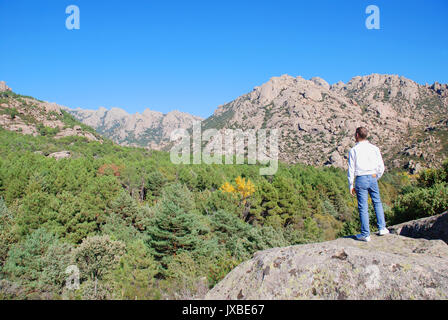 Man standing on a stone, watching the landscape. Parque Regional de la Pedriza de Manzanares, Manzanares El Real, - Stock Photo