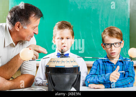 Two schoolboys and their teacher learning solar system in class at the desk against blackboard - Stock Photo