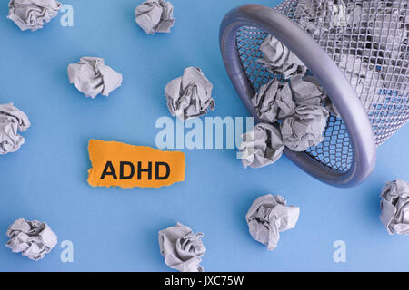 ADHD (Attention deficit hyperactivity disorder). Grey crumpled paper balls rolling out of a trash can. Close up. - Stock Photo