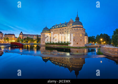 Medieval Orebro Castle reflecting in water in the evening, Orebro, Sweden - Stock Photo