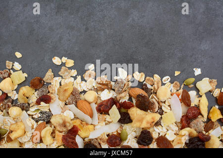 Muesli - cereal flakes with seeds, mixed fruit and nuts - in a border line with copy space on a dark grey slate - Stock Photo