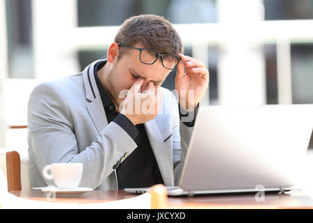 Tired executive suffering eyestrain working on line sitting in a coffee shop - Stock Photo