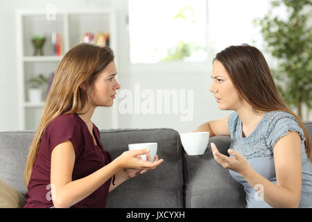 Two friends talking seriously sitting on a couch at home - Stock Photo
