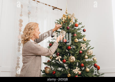 woman decorating christmas tree - Stock Photo