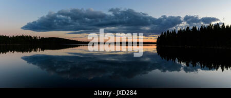 nice reflection of a large cloud during sunset at a Swedish lake. - Stock Photo