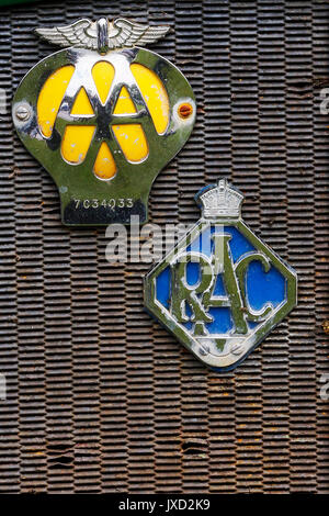 Vintage AA (Automobile Association) and RAC (Royal Automobile Club) badges mounted on a rusting radiator grill. - Stock Photo