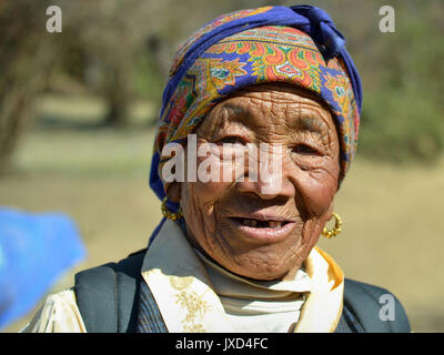 Closeup street portrait (outdoor headshot, full-face view) of an old Sherpa woman with traditional golden earrings; - Stock Photo
