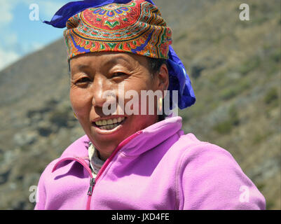 Closeup street portrait (outdoor headshot, three-quarter view) of a middle-aged Sherpa woman with traditional golden - Stock Photo