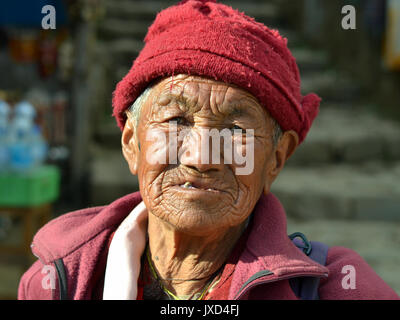 Closeup street portrait (outdoor headshot, full-face view) of an old Tibetan Buddhist nun from the Himalayas; Namche - Stock Photo