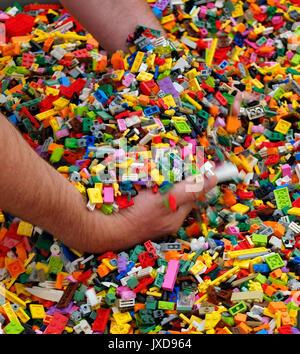 10.08.2017, Legoland Günzburg in Bayern, Ein Besucher greift in die große Schütte mit den bunten Legosteinen. (Modelreleased) - Stock Photo
