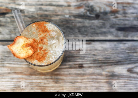 A drink with alcohol or without alcohol with cinnamon in decoration. This glass of cocktail is laid on a wooden - Stock Photo