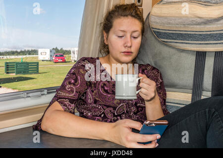 Pretty young woman drinking tea or coffee from a mug in a motorhome on a campsite. Exeter, Devon, England, UK. - Stock Photo