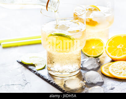 Homemade citrus lemonade in glasses with ice on slate. - Stock Photo